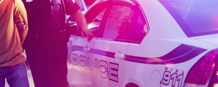 Police officer making an arrest, escorting a young man in handcuffs toward the back seat of his police car, at night.
