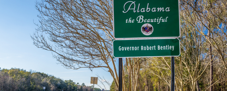 Welcome to Alabama road sign with highway in the background
