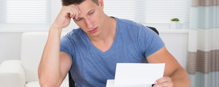 Young male stressed and confused looking at documents