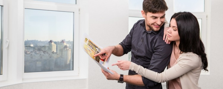Young couple viewing rental apartment and looking at apartment brochure